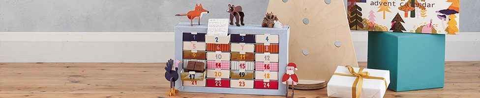 An advent calendar sits in front of a wooden Christmas tree and next to wrapped presents.