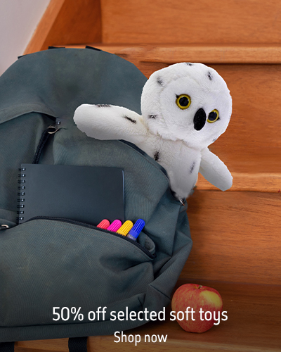 An owl soft toy sits in a child's backpack on the stairs. The text reads '50% off selected sft toys. Shop now'.