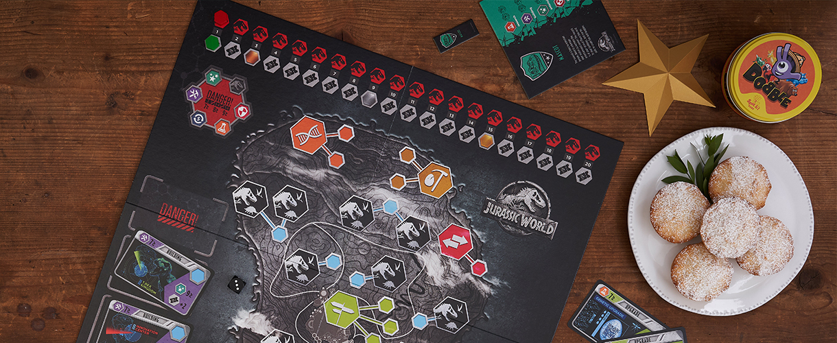 A Jurassic Park game sits on a wooden table alongside mince pies and gold paper stars.