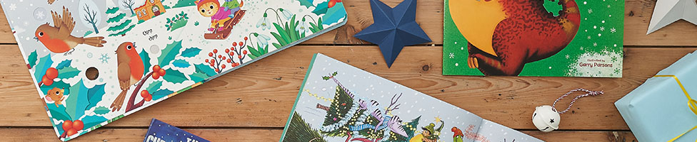 A close up of the corners of three Christmas books sat next to a paper star and metal bell.