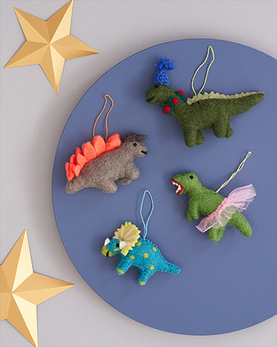 Felt Stegosaurus, Diplodocus, T. rex and Triceratops Christmas decorations sit on a blue background with gold paper stars.