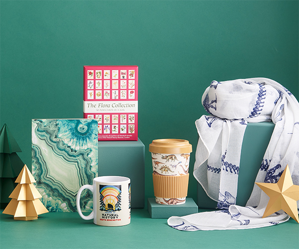 A selection of gifts for adults sit in front of a green background alongside gold paper trees and stars.