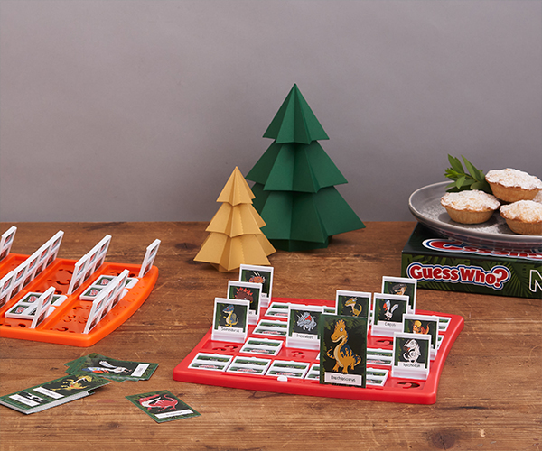 Dinosaur Guess Who sits on a wooden table with paper Christmas trees and a plate of mince pies.