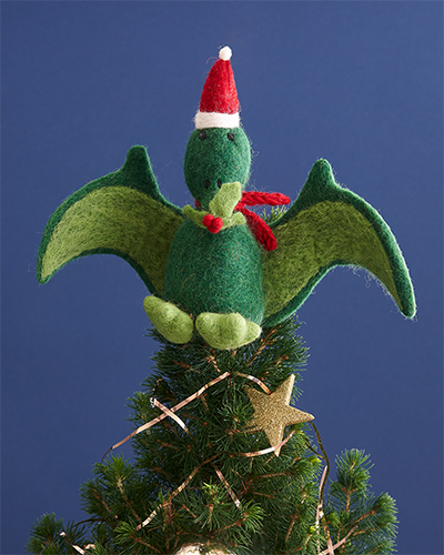 A Pteranodon tree topper sits on top of a small Christmas trees in front of a blue background.