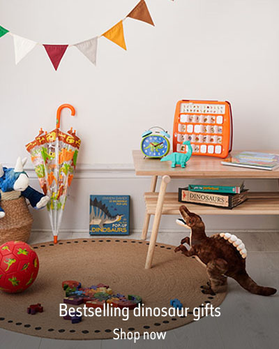 A room featuring multicoloured bunting, a brown rug and a wooden table. Dinosaur products fill the room. The text reads 'Bestselling dinosaur gits. Shop now.'
