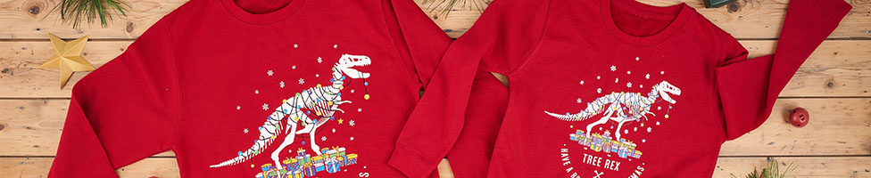 Two red T. rex Christmas jumpers on a wooden background