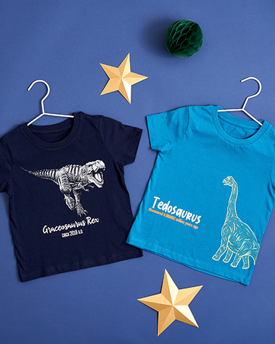Two personalised dinosaur t-shirts sit on a blue background alongside gold paper stars.
