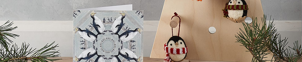 A penguin Christmas card sits next to a wooden Christmas tree decorated with hanging penguin decorations.
