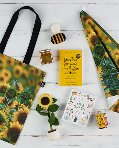 A range of bright sunflower and bee products lay on a white wooden background.