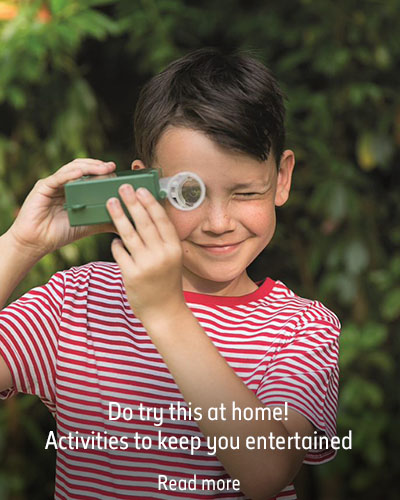 A boy in a striped t-shirt holds a microscope in front of blurred greenery. The caption reads 'Do try this at home! Activities to keep you entertained. Read more'.
