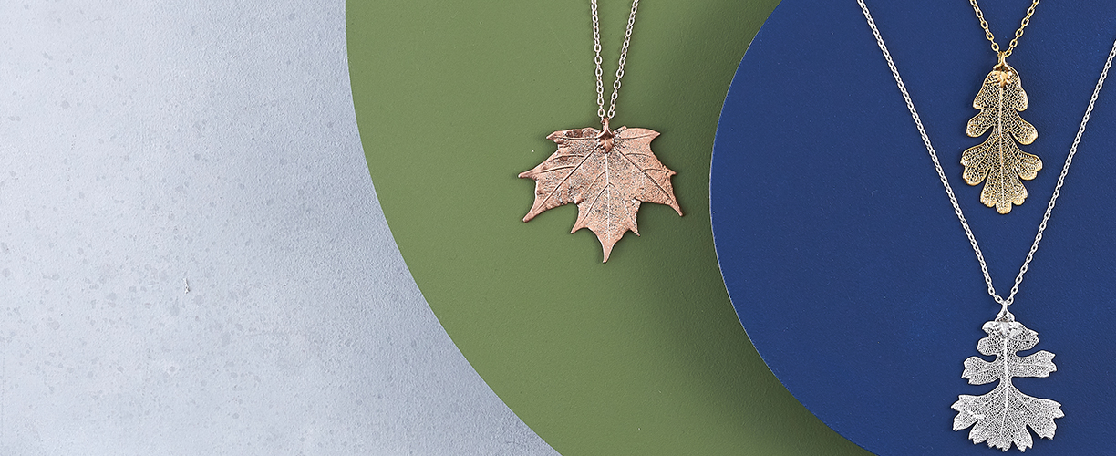 Leaf Jewellery on blue and yellow circular platforms against a mottled grey background