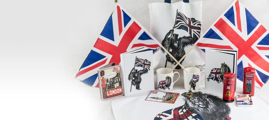 Best of Britain - Vintage London postcards, patriotic primate notebook, two mugs, patriotic lion notebook, post box tin, telephone box tin, tea towel and tote bag in between two Union Jack flags