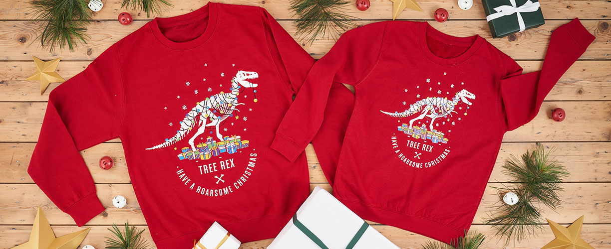 Two red dinosaur Christmas jumpers lay on a wooden background, surrounded by bells and branches