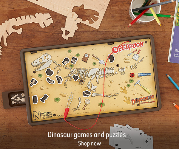 A Dinosaur Operation boardgame sits on a wooden table, surrounded by playing cards, pens and pencils. The text reads 'Dinosaur games and puzzles. Shop now'.