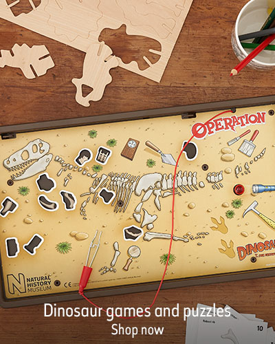 An Operation Dinosaur board game sits on a wooden table by a mug of pens. The text reads 'Dinosaur games and puzzles. Shop now.'