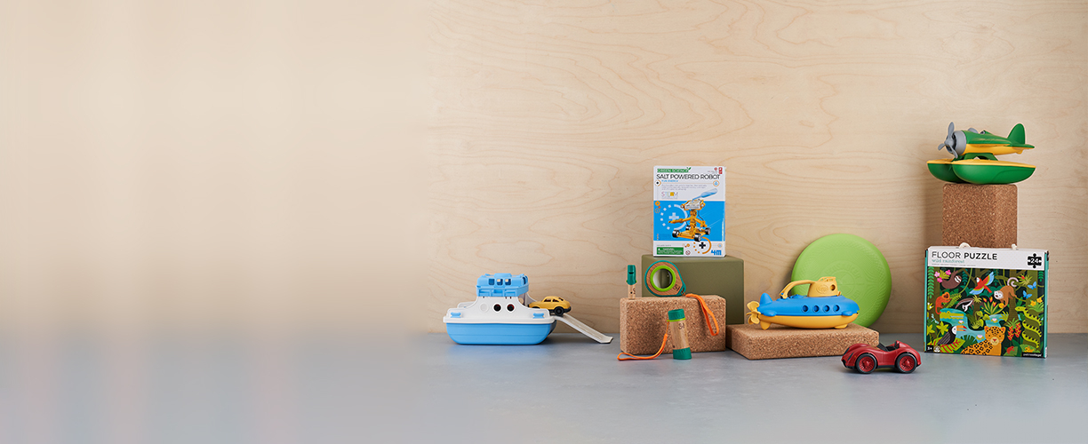 a selection of recycled plastic toys with eco friendly puzzles on grey shelf with a wooden background