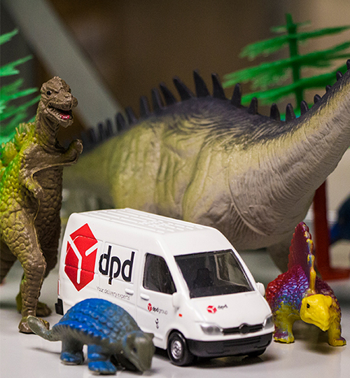 Toy DPD van surrounded by model dinosaurs