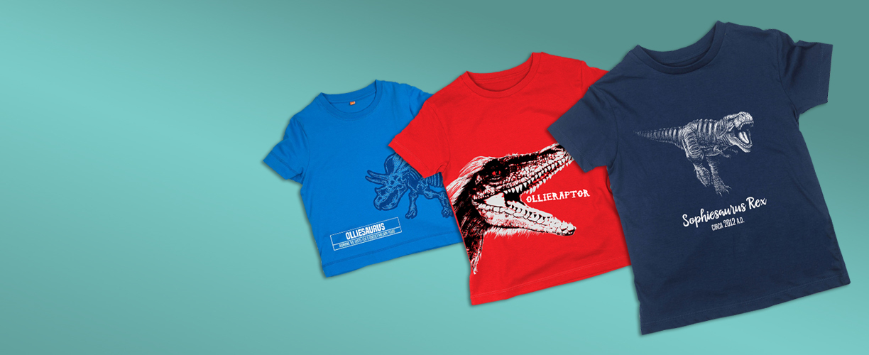 Three personalised dinosaur t-shirts spread out on a teal background.