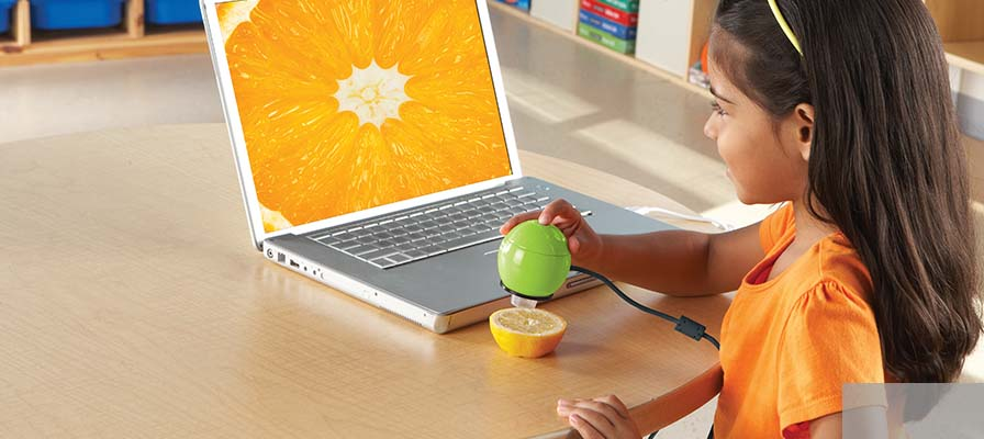 A child sitting in front of a laptop using a microscope to look at the detail of an orange segment.