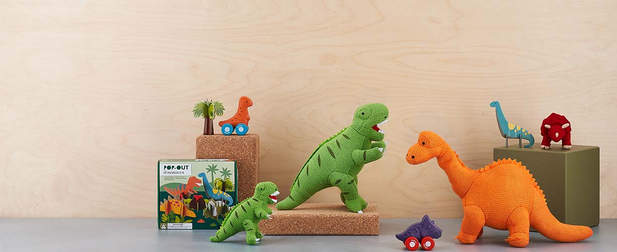 A selection of dinosaur toys in front of a pale wood background