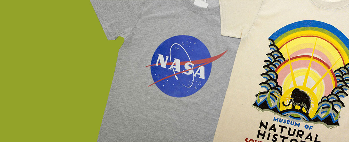 NASA logo t-shirt and vintage Natural History Museum t-shirt sit alongside each other on a green background